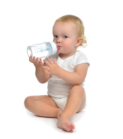 baby feeding: Infant child baby toddler sitting and drinking water from the feeding bottle on a white background Stock Photo