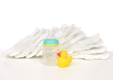 pampers: New born child stack of diapers nipple soother baby feeding milk bottle with water and yellow duck on a white background Stock Photo