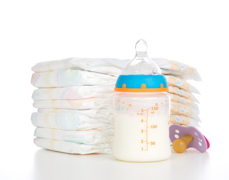 pampers: New born child stack of diapers nipple soother and baby feeding bottle with milk on a white background Stock Photo