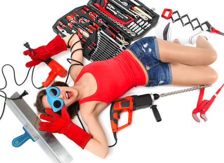 Happy sexy young woman contructor worker lying on a floor with construction set of tools wranches pliers drill spatula on a white background