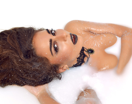 hair treatment: Closeup portrait of a sexy woman face lying smiling in white milk bath with splashes cream Stock Photo