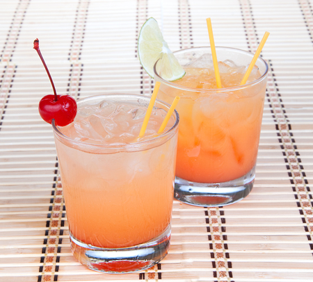 Alcohol margarita cocktails or long island Iced tea with lime in short cocktail glasses isolated on a white background