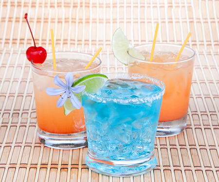 blue hawaiian drink: Alcoholic Cocktails. Three drinks beverages Blue lagoon tropical Martini tequila sunrise margarita with cherry lime pineapple juice and flower Stock Photo