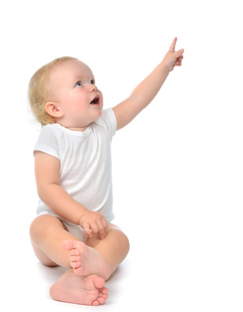 Infant child baby toddler sitting raise hand up pointing finger at the corner isolated on a white background Archivio Fotografico