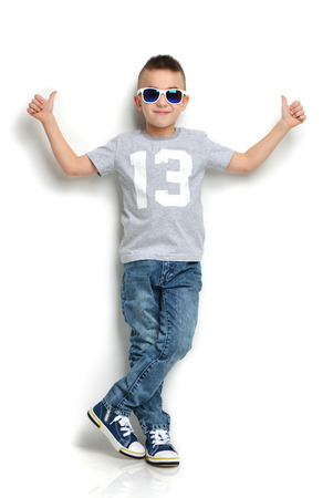 Moda niño hermoso en gafas de sol de los pantalones vaqueros de la camiseta de pie y da los pulgares para arriba signo más de fondo blanco Foto de archivo