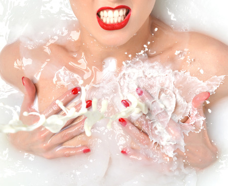 woman laying: Portrait of Fashion sexy woman angry face laughing with red lips and manicured nails smiling laughing in white milk bath spa with wave splashes on white background Stock Photo