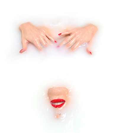 body milk: Portrait of Fashion sexy woman face with red lips and manicured nails smiling lying drawn in white milk bath spa with wave splashes on white background Stock Photo