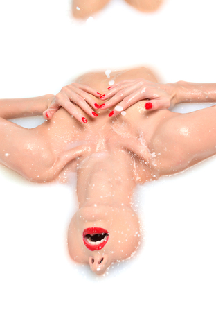 woman in bath: Portrait of Fashion sexy woman face laughing with red lips and manicured nails smiling laughing in white milk bath spa with wave splashes on white background Stock Photo