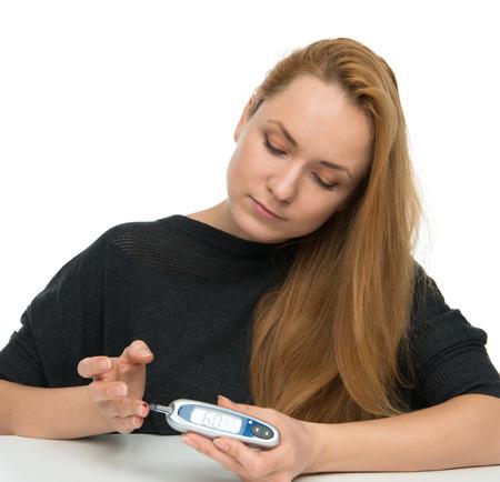 dedo: Diabetic prueba de medición paciente glucosa nivel mediante glucómetro mini ultra y pequeña gota de sangre de tiras de prueba y dedo aislado en un fondo blanco