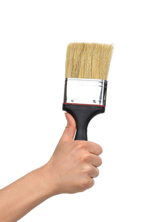 finger paint: Woman hand with paint brush with plastic black handle isolated on a white background
