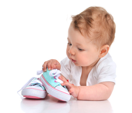 Infant child baby girl lying happy searching new shoes isolated on a white background