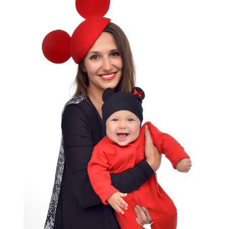 mom holding baby: Young mother woman holding in her arms new born infant child baby kid girl in red funny hat isolated on a white background