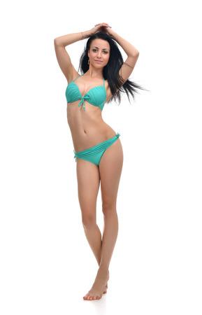 Счастливый молодая красивая женщина, полная брюнетка позирует в тело современной бикини swimsuite с ветреной волос, изолированных на белом фоне