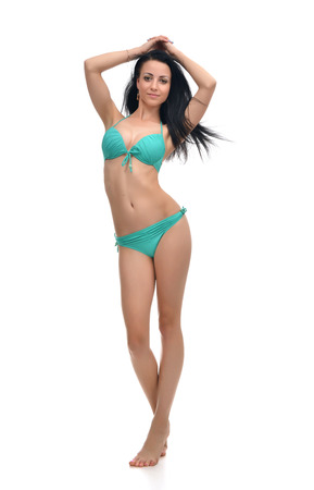 full body woman: Happy young beautiful full body brunette woman posing in modern bikini swimsuite with windy hair isolated on a white background