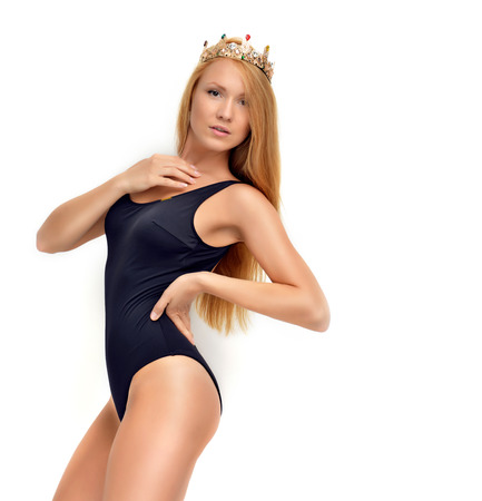 Sexy young beautiful red hair russian woman posing in black modern bikini swimsuit and rich crown with gems isolated on a white background