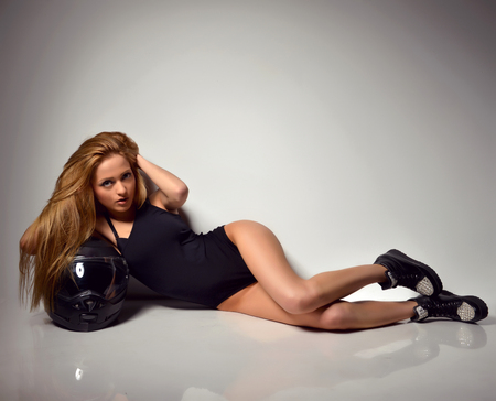 caucasian white: Sexy young beautiful full body blonde russian woman lying on the floor with black motorcycle helmet