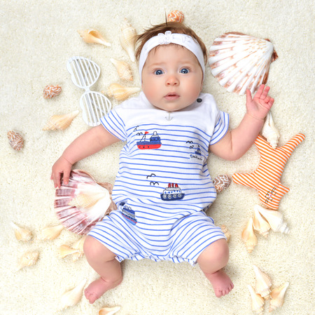 four month: Four month Infant child baby girl lying on a back happy with sea shore shells white sunglasses and small cat toy
