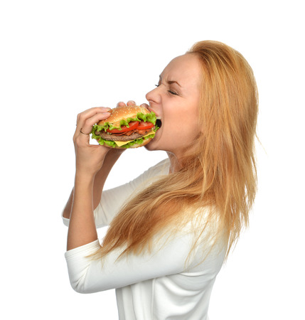 eating fast food: Fast food concept. Woman eating tasty unhealthy burger sandwich in hands hungry getting ready to eat isolated on a white background