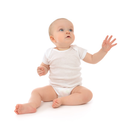 Infant child baby toddler sitting raise hand up pointing fingers looking at the corner isolated on a white background Foto de archivo