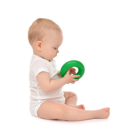 babies with toys: Infant child baby boy toddler playing holding green circle in hand on a floor on and looking up isolated a white background