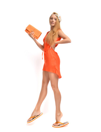 Young beautiful caucasian red hair woman walking in flip flops and  gorgeous orange dress with modern clutch isolated on a white background