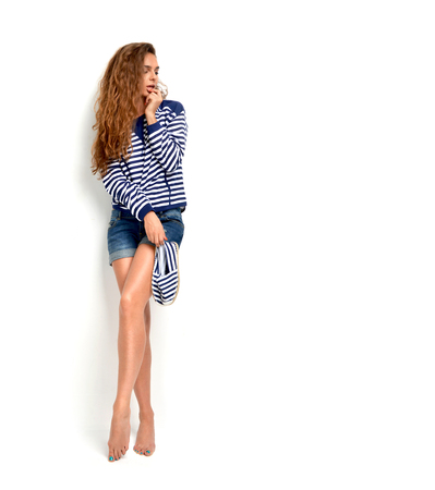 sexy fashion: Young happy caucasian brunette woman holding summer flip flops in blue stripes and jeans shorts isolated on a white background Stock Photo