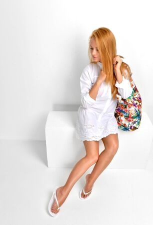 russian: Young beautiful caucasian red hair woman sitting in flip flops and gorgeous white dress with modern bag clutch on a white background Stock Photo