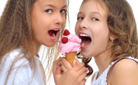 comiendo helado: Niñas jóvenes felices listos para comer rojo frambuesa helado en cono de gofres sonriendo gritos aislados en un fondo blanco