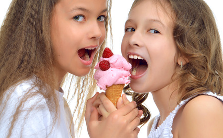 Young baby girls happy ready for eating red raspberry ice cream in waffles cone smiling yelling isolated on a white background Stock Photo