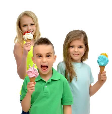 comiendo helado: Chicas jóvenes niños felices y chico listo comer rojo verde azul frambuesa helado de vainilla en gofres conos sonriente gritos aislados sobre un fondo blanco