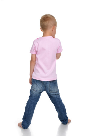 Rear view of caucasian full body american baby boy kid in pink tshirt and jeans isolated on a white background