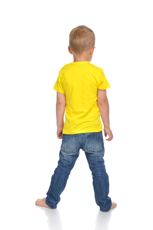 small butt: Rear view of caucasian full body american baby boy kid in yellow tshirt and jeans standing isolated on a white background