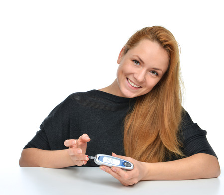 Diabetic patient measuring glucose level blood test using ultra mini glucometer and small drop of blood from finger and test strips isolated on a white background Reklamní fotografie