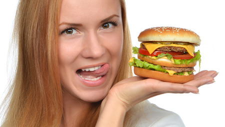 Fast food eating concept Woman hold cheeseburger sandwich with cheese salad tomatoes beef in hands hungry getting ready to eat isolated on a white background