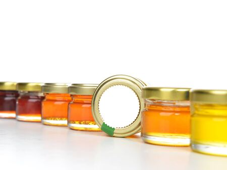 Tasty jars of jam and honey in a row with blank text space isolated on white background