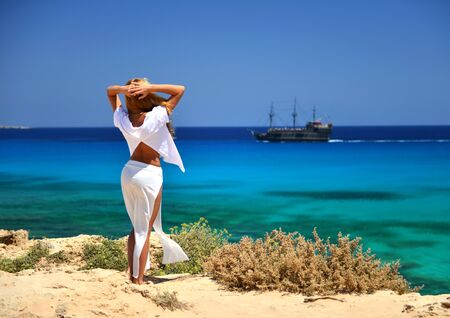Woman rear wiev looking at the blue mediterranean sea on Cyprus from the  back