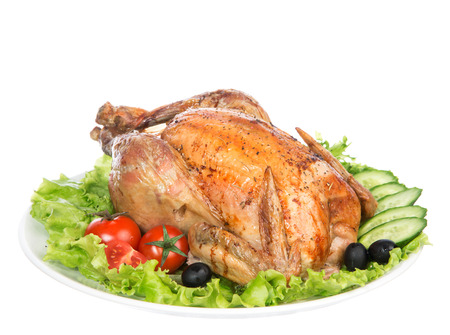 Garnished roasted thanksgiving chicken on a plate decorated with salad olives tomatoes cucumbers isolated on a white background
