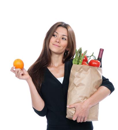 estilo de vida: Mulher nova que prende o saco de compra com mantimentos vegetais e frutas isoladas no fundo branco. Estilo de vida saudável comer conceito