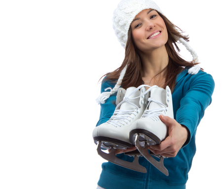 Young girl showing giving ice skates for winter ice skating sport activity in white hat happy smiling isolated on a white background Foto de archivo