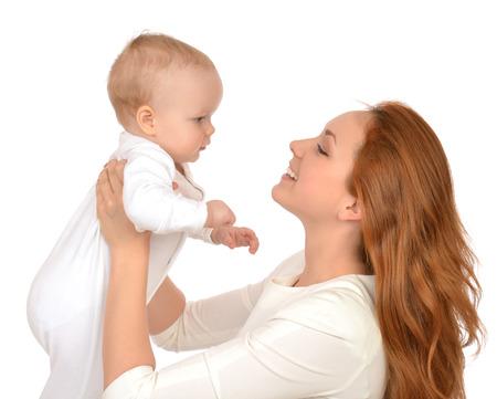 Mujer Joven madre celebración de abrazos en brazos bebé bebé niño chico sonriente niña riendo sobre un fondo blanco Foto de archivo