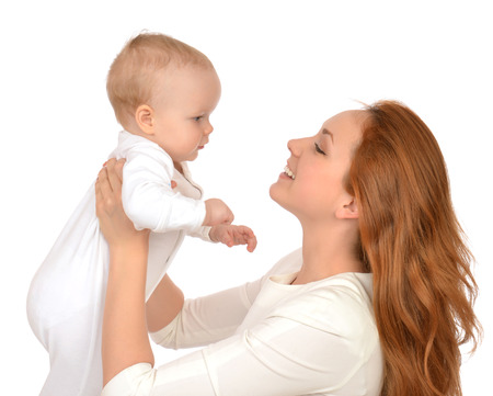 Young mother woman holding and hugging in her arms infant child baby kid girl smiling laughing on a white background