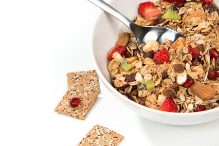 avena: Cereales muesli tazón y cuchara con almendras, piñones, nueces, pasas, avena y trigo copos, pasas, frutas frescas kiwi, piezas de fresa, plátano, semillas de granada
