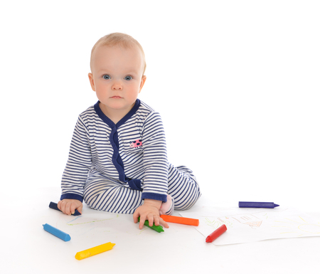 baby sitting: Infant child baby toddler sitting drawing painting with color pencils crayons on a white background