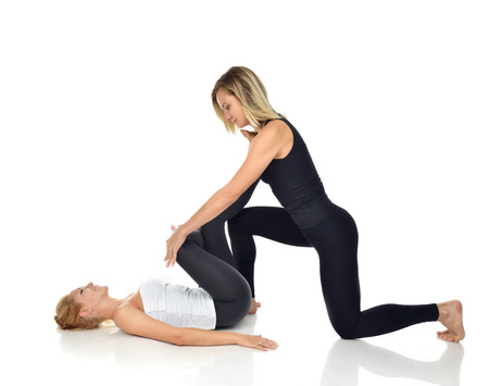 sport woman: Doctor physiotherapist stretching a young sport woman isolated on a white background
