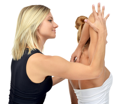 physical therapy: Doctor physiotherapist stretching a young sport woman isolated on a white background