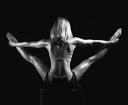Young sport yoga woman back view posing while doing gymnastic split black and white picture