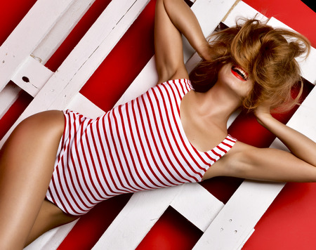 Young happy beautiful sexy woman posing lying in summer fashion body cloth laughing on wooden pallet on red background Stock Photo