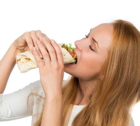 eating: Woman eating tasty unhealthy burger twisted sandwich in hands hungry getting ready to eat isolated on a white background Fast food concept