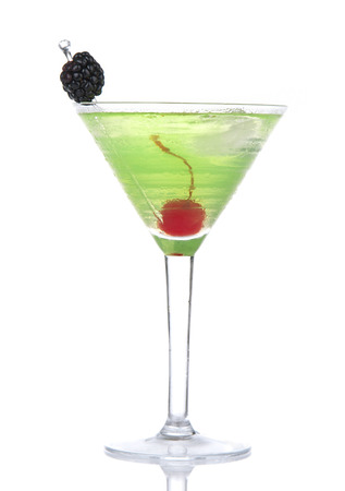 blue hawaiian drink: Green alcohol cosmopolitan cocktail decorated with maraschino cherry and blackberry in martini cocktails glass isolated on a white background