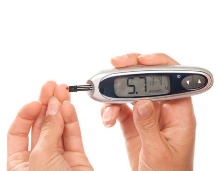 diabetes: Prueba de la diabetes en la sangre del paciente el nivel de glucosa de medición utilizando glucómetro mini ultra y pequeña gota de sangre del dedo y prueba stripsand dispositivo mostrando 5,7